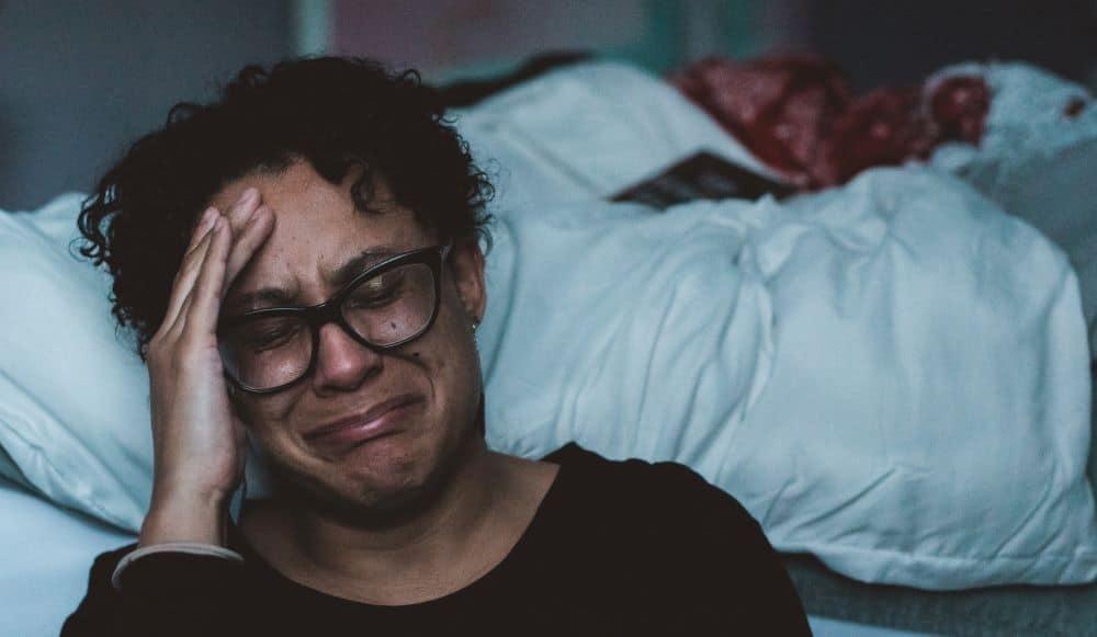 Mann sitzt vor dem Bett und weint