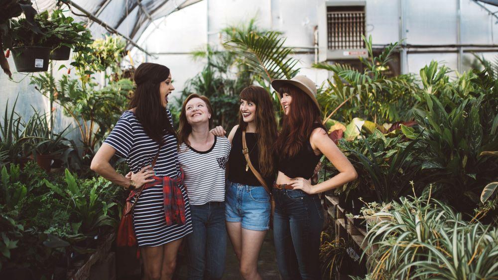 4 Frauen stehen nebeneinander und lachen