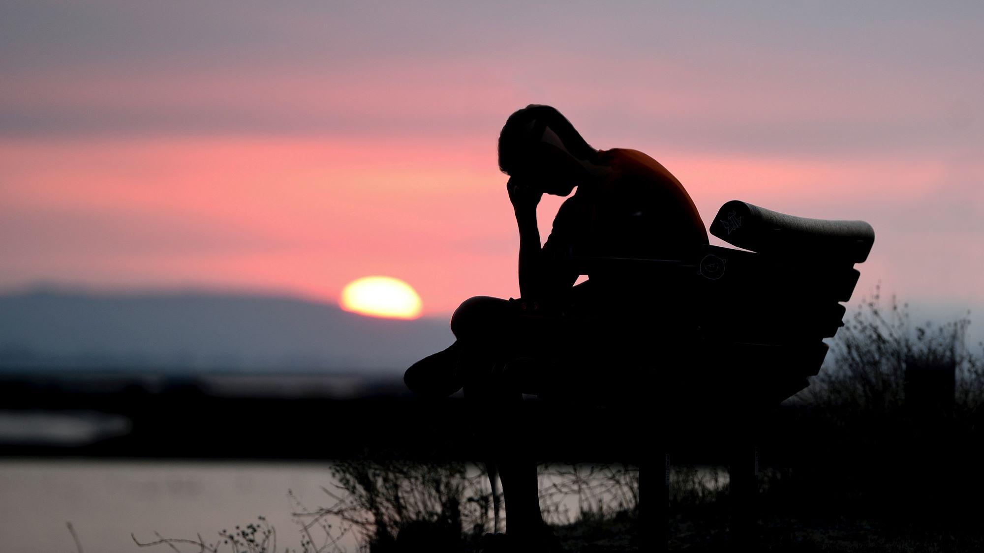 Mann sitzt auf einer Bank und hält sich den Kopf