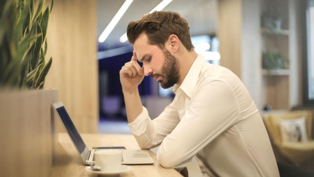 Mann sitzt vor einem Notebook und prüft sein Online-Dating Profil