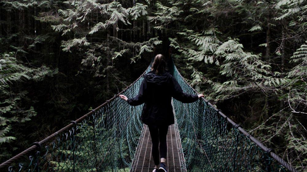 Frau auf Brücke mit Blick in den Dschungel der die schwiew