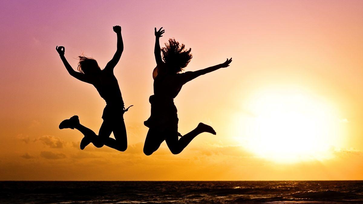 2 Personen springen Glücklich in die Luft vor einem Sonnenuntergang