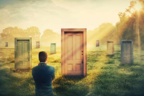 Mann steht vor mehreren Türen als Symbolbild für die Aiswahl der richtigen Partnerbörse