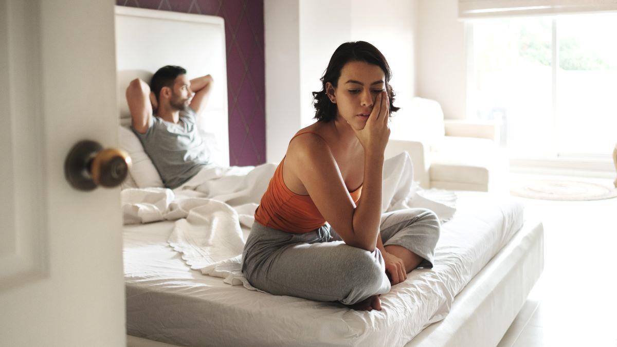 Mann und Frau auf dem Bett voneinander abgewandt