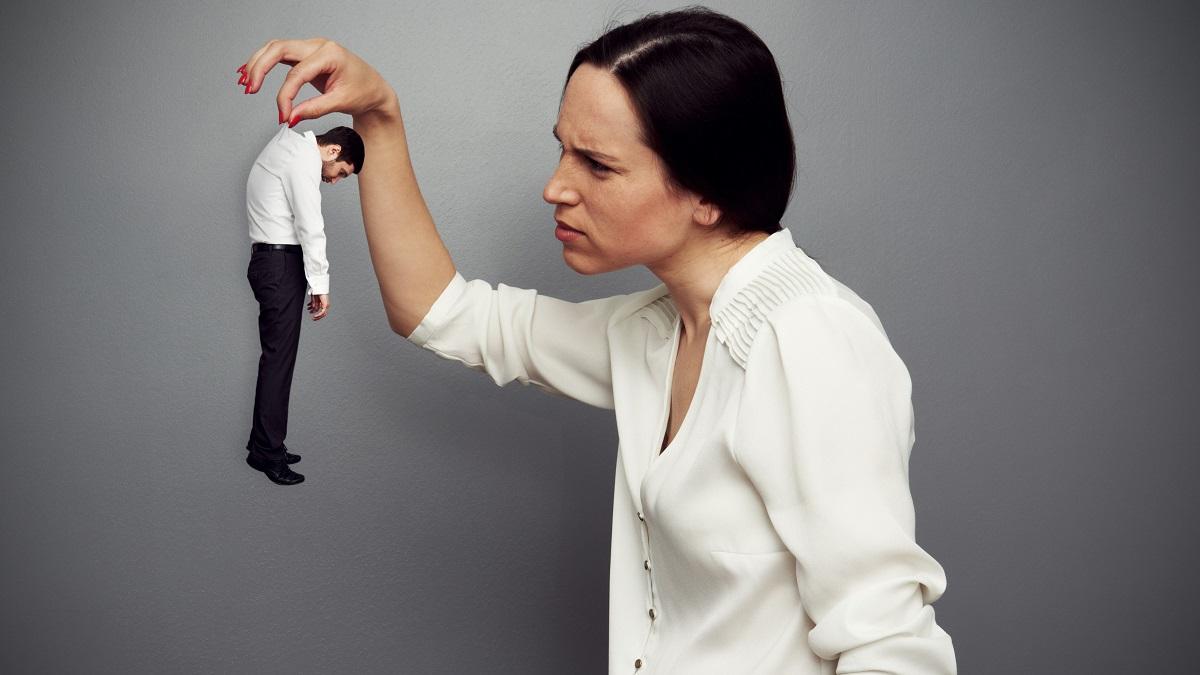 Übergroße Frau hält kleinen Mann dominant mit der Hand im Genick